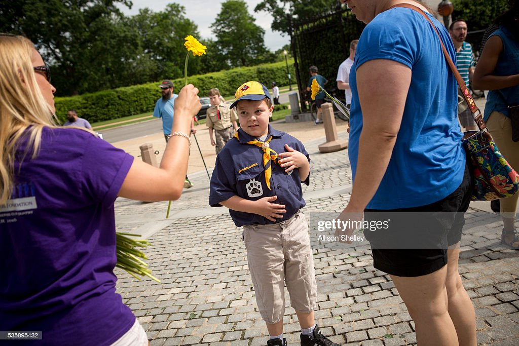 Dana Armellini, left, 28, gives a flower to a Boy Scout at the visitors center at Arlington National Cemetery on May 30, 2016 in Arlington, Virginia. Volunteers from the Memorial Days Flowers Foundation place flowers on graves the cemetery and hand out thousands more to visitors on Memorial Day.
