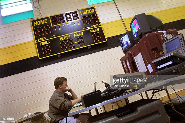 Dana Hill an associate producer for ABC News works under the score board in the media center April 12 2001 at the Crawford Texas elementary school...