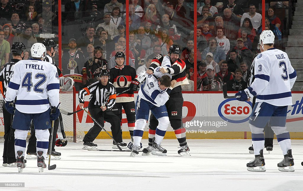 Dana Tyrell and Keith Aulie #3 of the Tampa Bay Lightning watch teammate B.J. Crombeen #19 fight with Matt Kassian #28 of the Ottawa Senators as Erik Condra #22 of the Ottawa Senators looks on, March 23, 2013 at Scotiabank Place in Ottawa, Ontario, Canada.