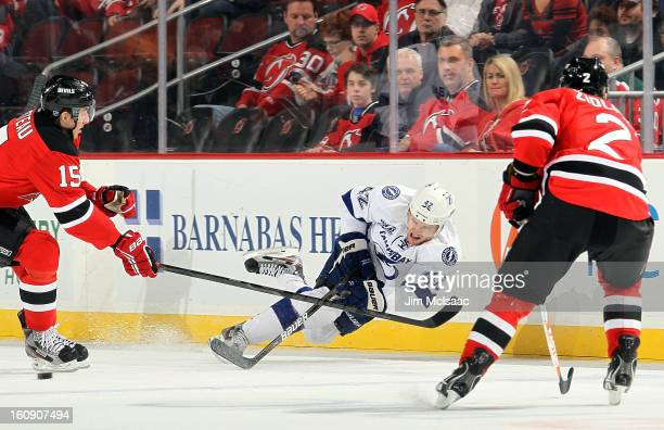 Dana Tyrell of the Tampa Bay Lightning plays the puck in the first period against Stefan Matteau and Marek Zidlicky of the New Jersey Devils at the...
