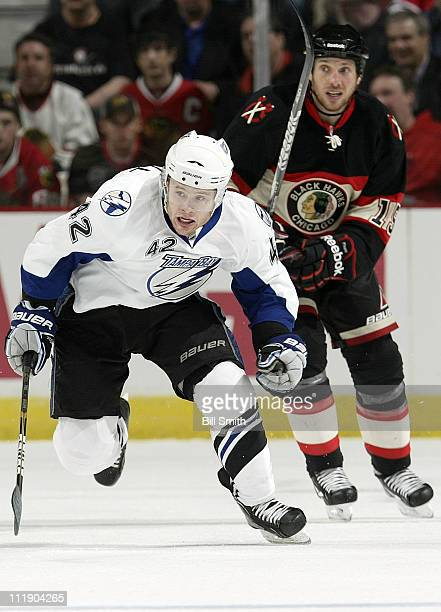 Dana Tyrell of the Tampa Bay Lightning races toward the puck as Fernando Pisani of the Chicago Blackhawks watches in the background on April 3 2011...