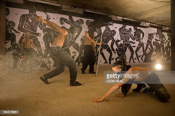 A dance group called 'The Bonebreakers' perform in front of an artwork by artist Cleon Peterson during a photocall for the exhibition 'Brutal' at the...