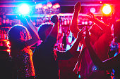 Group of dance lovers enjoying disco in nightclub