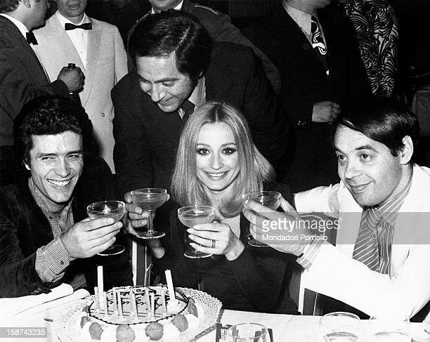Dancer and presenter Raffaella Carrà celebrating her birthday with a cake and candles in front of her and toasting with Gianni Nazzaro Corrado and...
