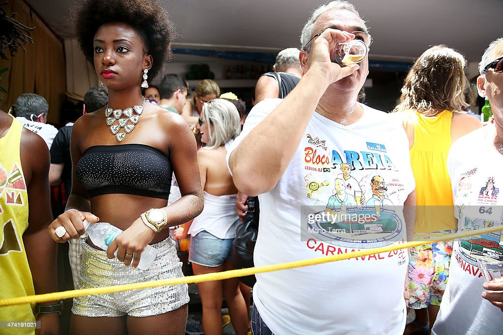 Dancer Carola Pretinha (L) stands at a 'bloco' party during pre-Carnival festivities on February 22, 2014 in Rio de Janeiro, Brazil. Carnival officially begins on February 28 but pre-festivities have already begun.