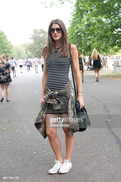 Dancer Erin Dusek wears Ray Ban sunglasses converse trainers Topshop dress jacket and bag at Lovebox 2015 on July 17 2015 in London England