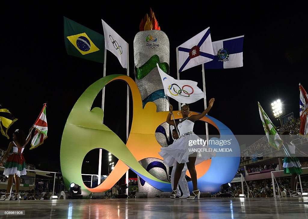 A dancer flutters the Olympic flag during the opening ceremony on the first day of parades at the Sambadrome in Rio de Janeiro, Brazil on February 7, 2016. AFP PHOTO/ VANDERLEI ALMEIDA / AFP / VANDERLEI ALMEIDA
