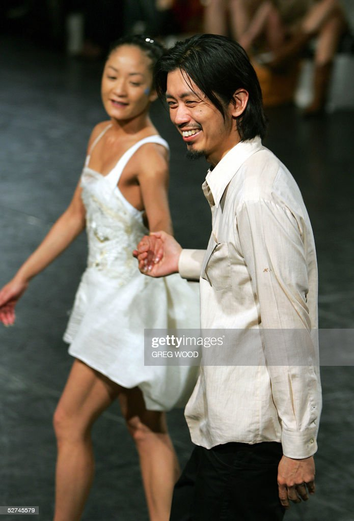 A dancer from the Sydney Dance Company wears a creation by Australian designer Akira Isogawa who acknowledges the applause of guests following his...