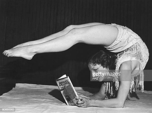 Dancer Gertrude Fisher laying with her legs bent over her head to read her husbands latest novel 'Marquee Ballyhoo' 1932