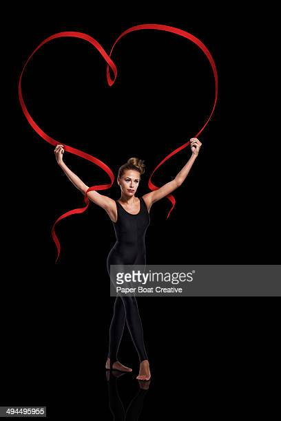 Dancer holding red ribbon shaped as a heart