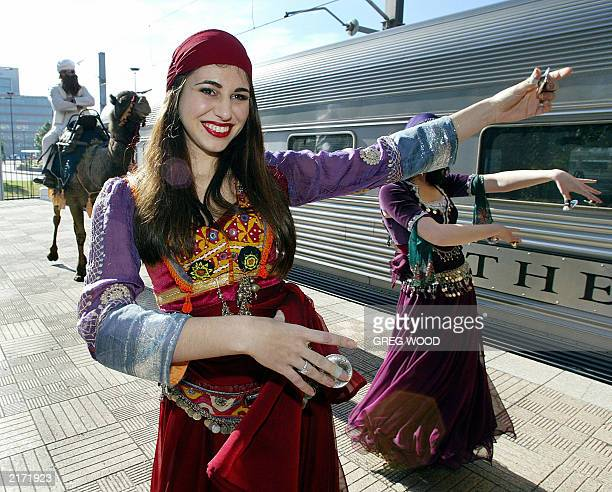 Dancer Jane Jardine followed by a camel performs at a Sydney launch for a new train service 19 June 2003 'The Ghan' train which has been running for...