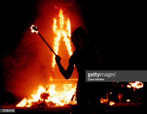 A dancer juggles fire as a 52foot tall wooden man as it goes up in flames September 2 2000 during the15th annual Burning Man festival in the Black...