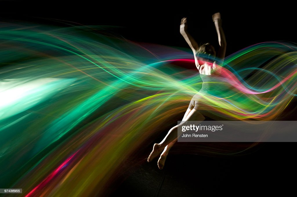 dancer jumping in abstract green light trails : Stock Photo