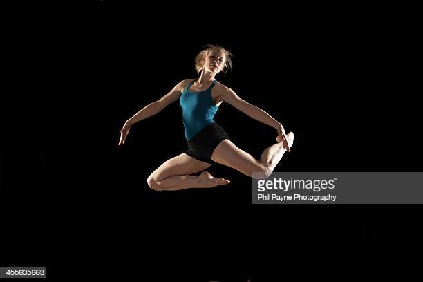 Dancer jumping on black background