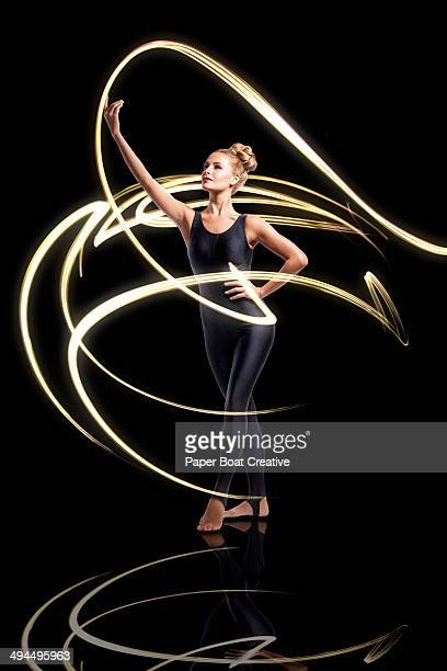 Dancer moving with bright light beams all around