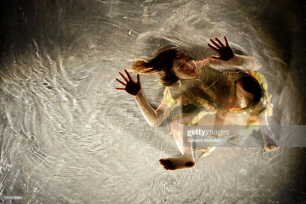 A dancer of acclaimed Argentinian group Fuerzabruta performs in a piece entitled 'Mylar', while being suspended on a translucent 15m pool during Singapore's 5th annual Night Festival on August 31, 2012 in Singapore.