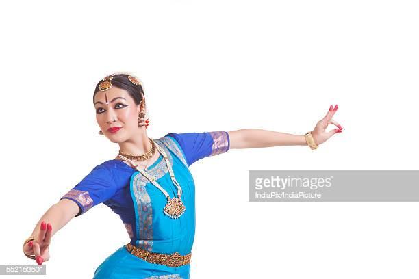 Dancer performing Bharatanatyam against white background