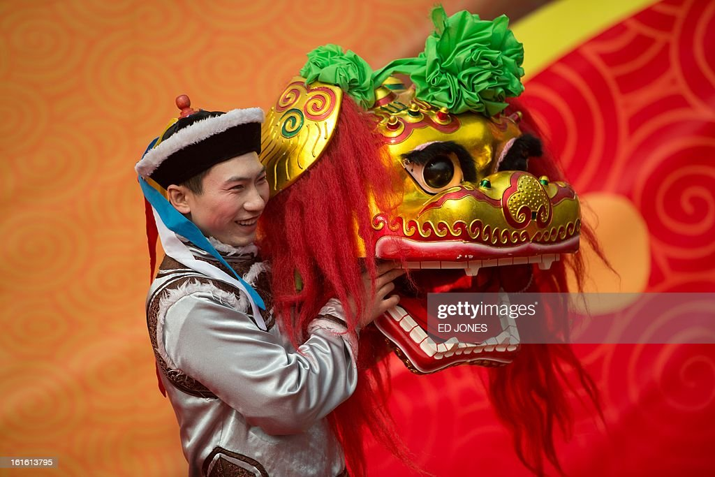 A dancer poses with a 'lion' head prior to a show at a temple fair at Longtan park in Beijing on February 13, 2013. A billion-plus Asians are ushering in the lunar Year of the Snake with a week of festivities. AFP PHOTO / Ed Jones