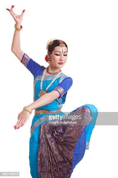 Dancer posing while performing Bharatanatyam against white background