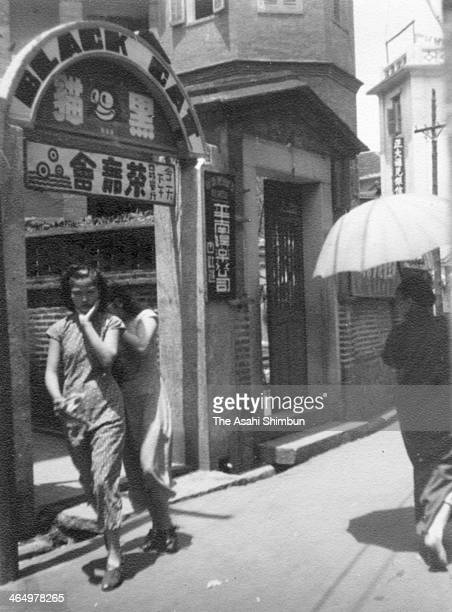 A dancer stands outside the Black Cat Dance Hall on unspecified time@on Gulangyu Island in Xiamen China