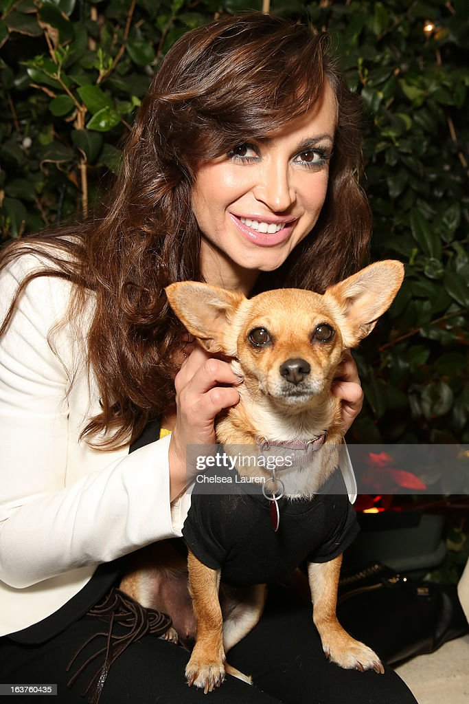 Dancer / TV personality Karina Smirnoff poses with a dog wearing Lyric Culture for PetSmart at Much Love Animal Rescue's makeovers for mutts at Peninsula Hotel on March 14, 2013 in Beverly Hills, California.