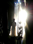 On the side of a stage, a female dancer waits to go out into the bright lights of the stage.