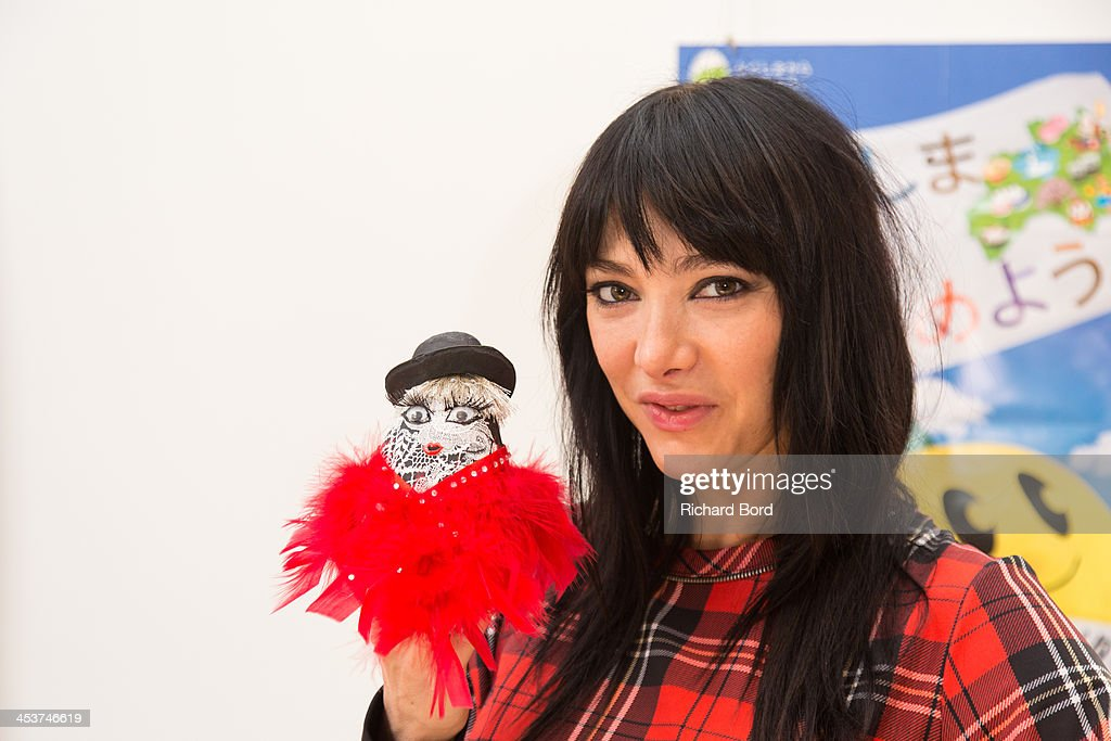 Dancer Zula of the Crazy Horse pose with the traditional Doll 'Okiagari Koboshi' she has decorated during the 'Solidarite Fukushima' exhibition in tribute to the victims of Fukushima on December 5, 2013 in Paris, France.