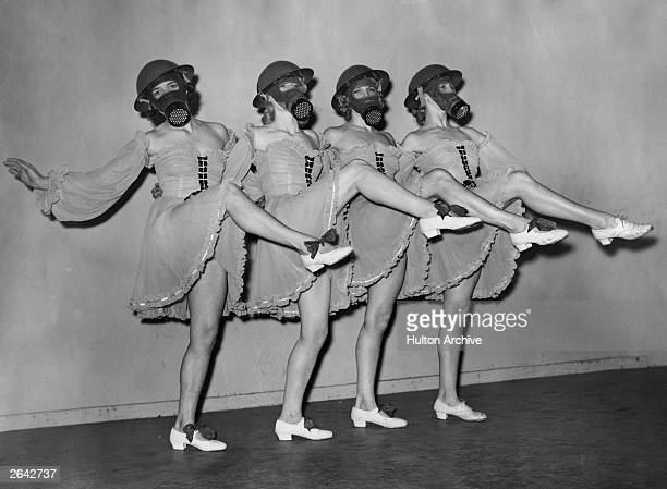 Dancers at the Windmill Theatre in London practice a routine wearing gas masks and hardhats with their costumes