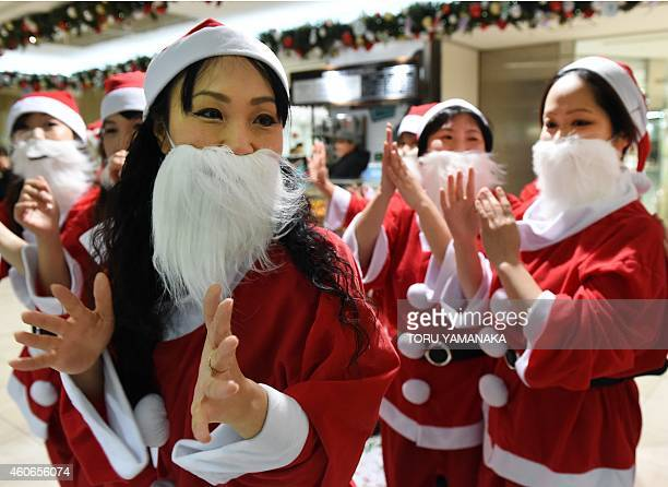 Dancers clad in Santa Claus outfits perform as part of a flash mob event to entertain Christmas shoppers at Tobu Department Store in Tokyo on...