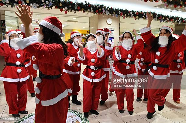 Dancers clad in Santa Claus outfits performs as part of a flash mob event to enjoy Christmas shoppers at Tobu Department Store in Tokyo on December...