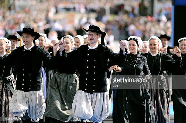 Dancers dressed with folk costumes from Brittany perform a traditional Breton dance on August 5 2012 in Lorient French Brittany during the...