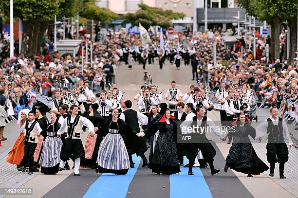 Dancers dressed with folk costumes from Brittany perform a traditional Breton dance as musicians of a traditional Bagad band perform on August 5 2012...