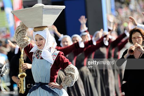 Dancers dressed with folk costumes perform a traditional Breton dance on August 5 2012 in Lorient French Brittany during the traditional street...