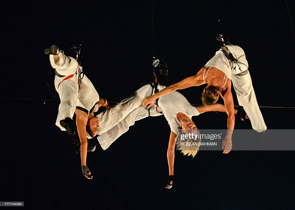 Dancers from the Compagnie Retouramont perform 'Pyramid of Void' while suspended in mid-air during a media preview of the Singapore Night Festival on August 21, 2013. The sixth edition of the Singapore Night Festival to be held over two weekends in August consist of an eclectic mix of aerial performances, art and light installations, roving acts and heritage-inspired programmes by local and international performers.