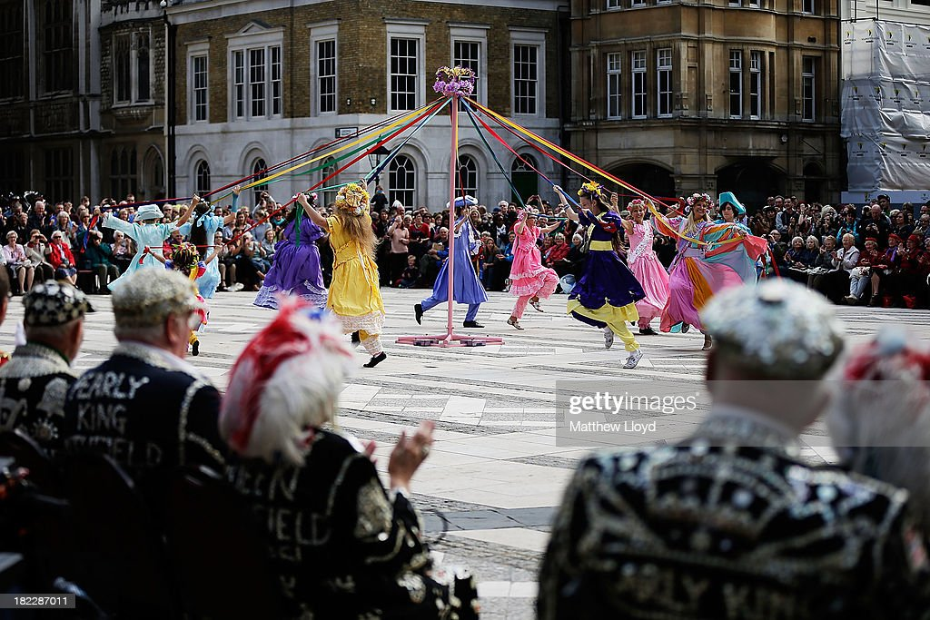 Dancers in traditional costumes perform to the crowd in the Guildhall Yard on September 29, 2013 in London, England. The Harvest Festival features dancing and entertainment by participants in traditional costumes and concludes with a service at St Mary-le-Bow Church, home of the renowned Bow Bells. Dressing as a Pearly King or Queen, by wearing clothes adorned with pearl buttons, originated in the 19th century when London street sweeper Henry Croft decorated his uniform and began collecting money for charity