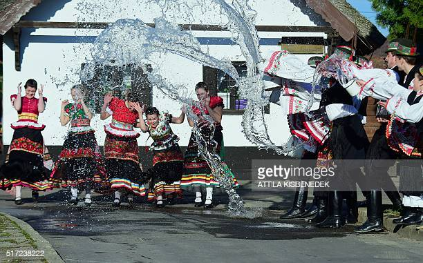 Dancers of 'Matyo Folklor Art Association' in traditional clothes react as boys throw water in Mezokovesd some 130 km east of Budapest on March 24...
