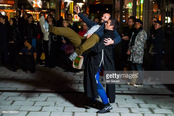 A dancers of the Boris Charmatz Company carries off an audience member as they perform 'Musee de la danse Ñ danse de nuit' at the multi story car...