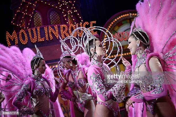 Dancers of the Moulin Rouge discuss after performing on October 1 2014 at the Moulin Rouge cabaret in Paris Cradle of French Cancan immortalized by...