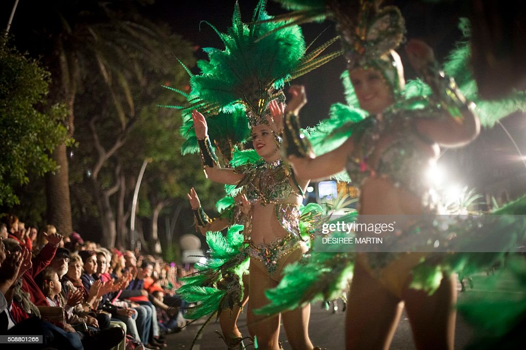 Dancers parade in the street during the Rhythm and Harmony contest in the Carnival of Santa Cruz de Tenerife on the Spanish Canary island of Tenerife on February 7, 2016. The dresses are more than five meters high and over 80 kilos in weight. The event began on January 13 and finishes on February 14 with orchestras playing Caribbean and Brazilian rhythms throughout the festivities that range from elections for the Carnival Queen, the Junior Queen and the Senior Queen, to children and adult murgas (satirical street bands), comparsas (dance groups) and street performances. AFP PHOTO / DESIREE MARTIN / AFP / DESIREE MARTIN