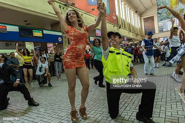 Dancers perform at the central station during a flash mob for the National Samba Day in Rio de Janerio Brazil on December 2 2013 AFP PHOTO/YASUYOSHI...