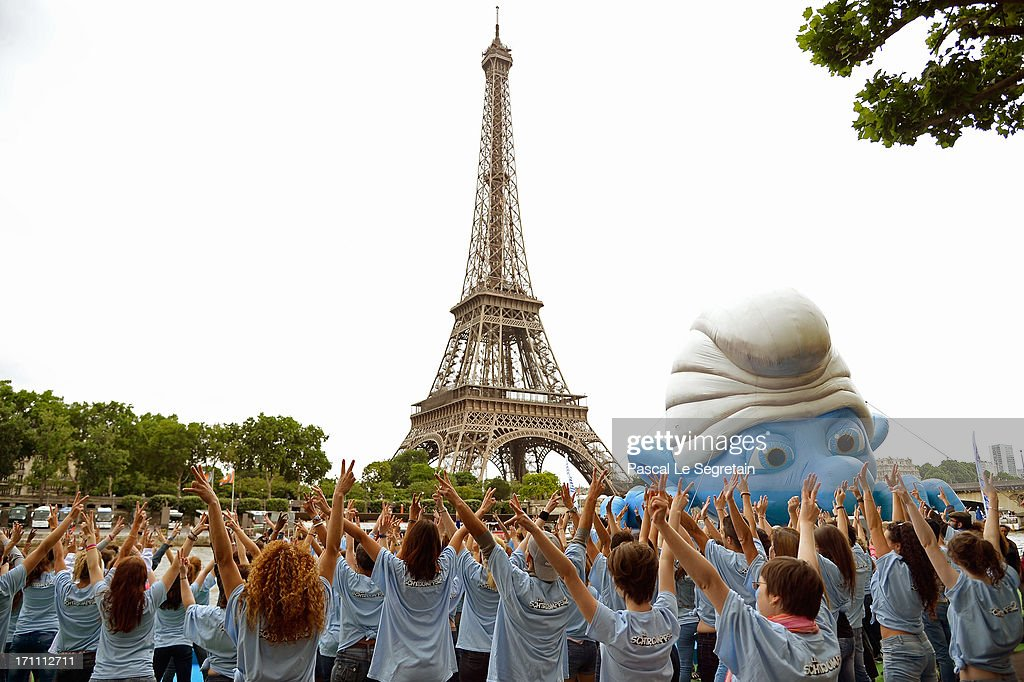 Dancers perform by a giant Smurf character as part of Global Smurfs Day celebrations on June 22, 2013 on the Seine river bank in Paris, France.