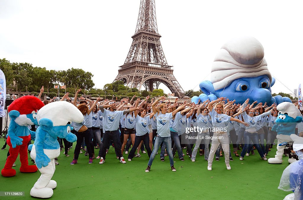 Dancers perform by a giant Smurf character as part of Global Smurfs Day celebrations on June 22, 2013 on the Seine river bank in Paris, France. The Eiffel tower is seen behind.