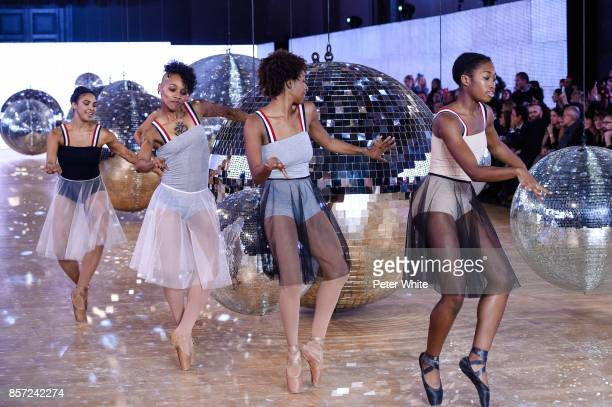 Dancers perform on the runway during the Moncler Gamme Rouge Paris show as part of the Paris Fashion Week Womenswear Spring/Summer 2018 on October 3...