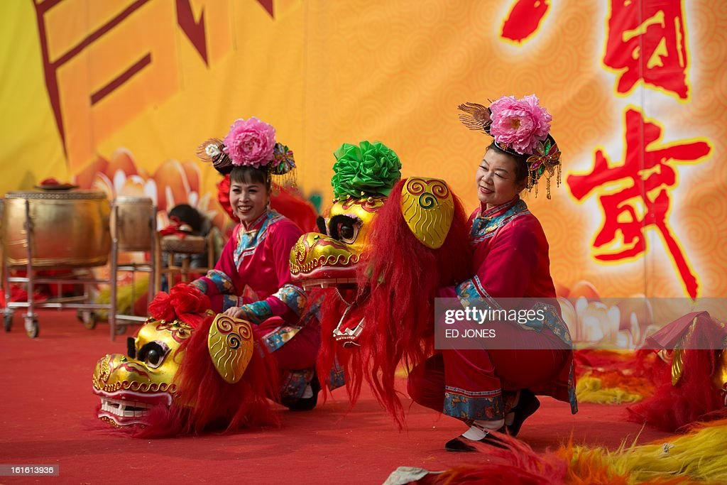 Dancers pose with 'lion' heads on stage prior to a performance at a temple fair at Longtan park in Beijing on February 13, 2013. A billion-plus Asians are ushering in the lunar Year of the Snake with a week of festivities. AFP PHOTO / Ed Jones