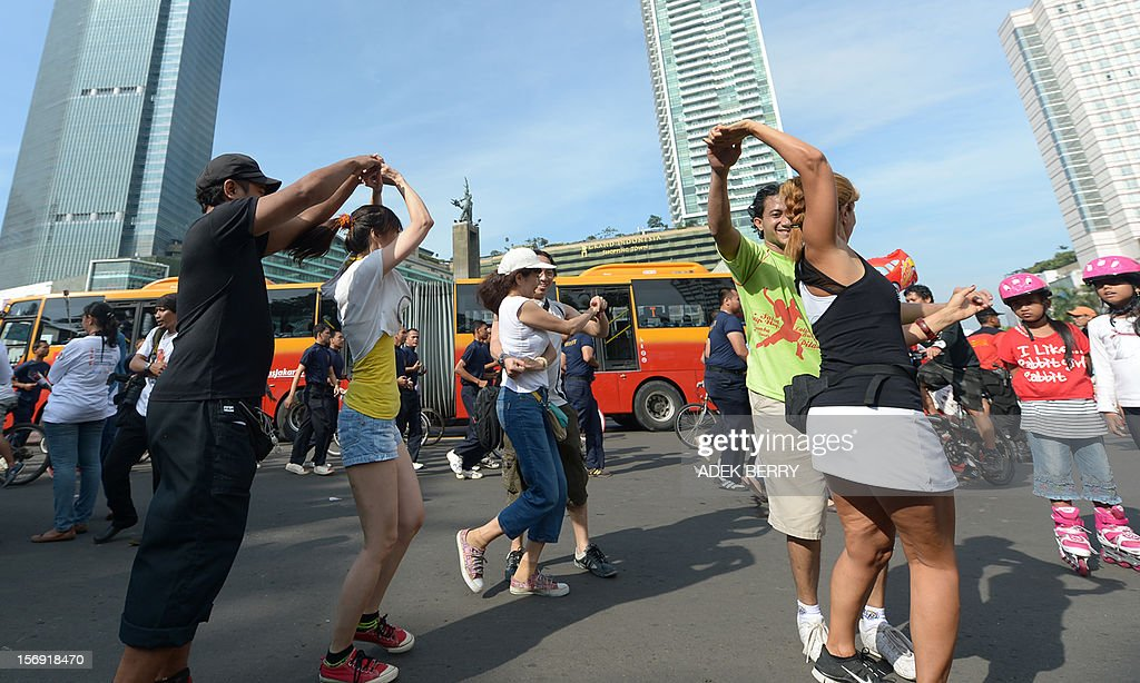 Dancers practice salsa dancing as Jakarta residents walk on a road on car-free day in Jakarta on November 25, 2012. Car free day began in 2007 and is held in Jakarta's main avenues to reduce the number of vehicles on the roads, allowing residents to enjoy their activities along a street which usually congested with vehicles during the week. AFP PHOTO / ADEK BERRY
