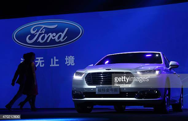 Dancers walk near a Ford Motor Co Taurus sedan displayed at a media event ahead of the 16th Shanghai International Automobile Industry Exhibition in...