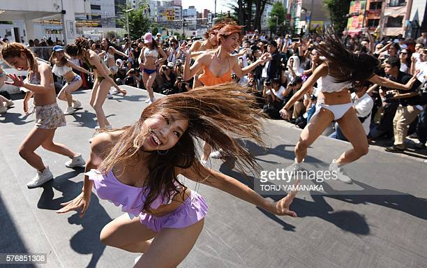 TOPSHOT Dancers wearing new bikinis perform in front of passersby and a line of photographers during a promotional flash mob event on a square...