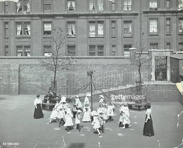 Dancing around the maypole Hugh Myddelton School Finsbury London 1906 Children dance around a maypole in the school playground watched by two...