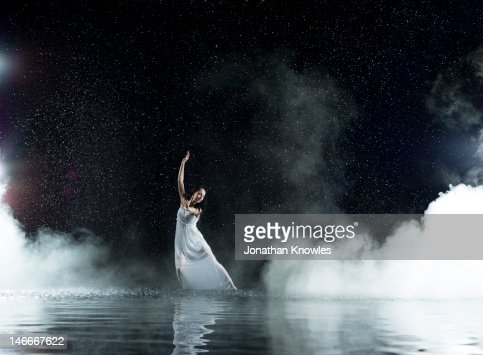 Dancing female in water, rainy and misty night : Stock Photo