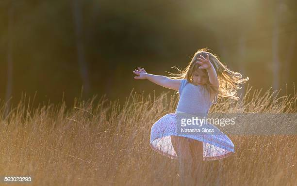 Dancing in a field at sunset
